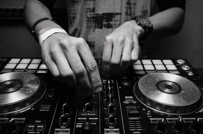 Black and white image of a pair of hands working a mixer and EQ